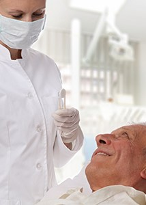 Older man smiling up at dentist