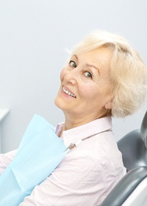 Senior dental patient holding mirror, admiring her implant-retained dentures