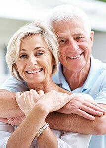 Older couple holding each other smiling