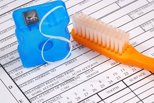 toothbrush and floss on dental insurance forms