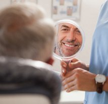 smiling dental patient looking in mirror