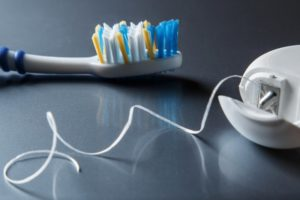 Floss container sitting beside a toothbrush on a dark surface
